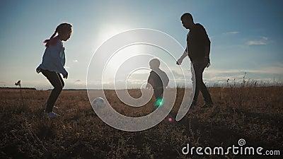 Padre y dos niños que juegan en el campo con el balón de fútbol Concepto de deporte almacen de metraje de vídeo