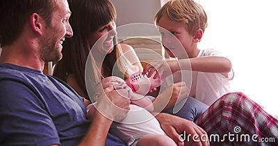 Padres con el bebé de alimentación del hijo en cama con la botella almacen de video