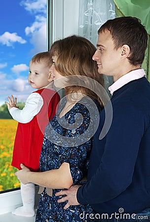 Padres con el niño que mira hacia fuera la ventana