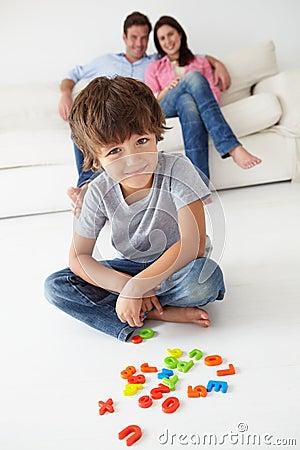 Padres que miran el juego del hijo