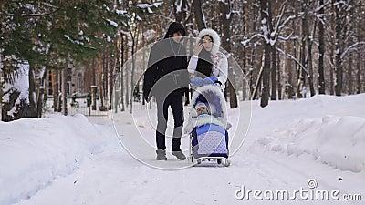 Padres vestidos hermosos jovenes que caminan en parque nevado con su niño que se sienta en el carro de bebé por el esquí almacen de video