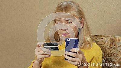 Paga mayor de la mujer para las compras en la tarjeta de crédito bancaria de Internet Ella introduce cuidadosamente un número de  almacen de video