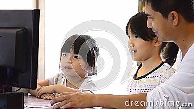 Pai asiático And Cute Daughter que joga o computador vídeos de arquivo