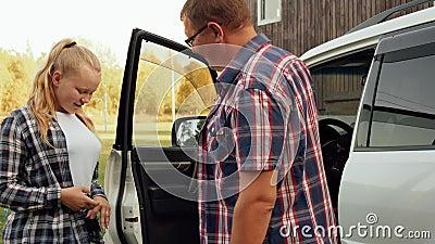 Pai dando chaves de carro para a adolescente filha por andar Menina que recebe chave de carro do pai por dirigir video estoque