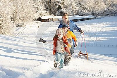Pai e crianças que puxam o Sledge acima do monte nevado