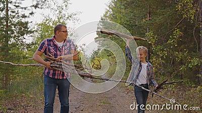 Pai e filho colecionando madeiras secas na floresta de verão no acampamento Amigo pai e filho segurando lenha e pau-brasil filme