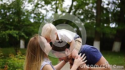 Pai novo alegre feliz da família, mãe e filho pequeno tendo o divertimento fora, jogando junto no parque do verão video estoque