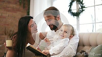 Pai novo e seu livro de leitura do filho, quando a mãe beber o chá e beijar seu marido Natal da leitura da família vídeos de arquivo