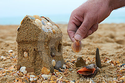 Pai que constrói uma casa da areia em um seashore