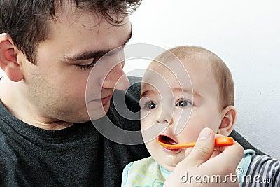 Pai que dá o alimento a seu bebê