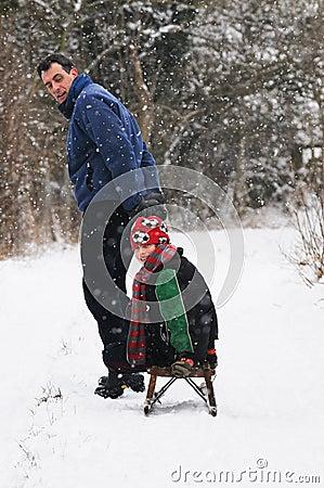 Pai que puxa o filho no sledge