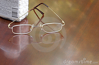 Pain relievers and reading glasses on desk