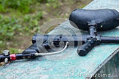 Paintball gun lies under drizzle.