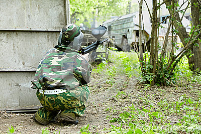 Paintball player in camouflage hides