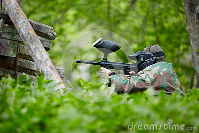 Paintball player in camouflage sits in ambush