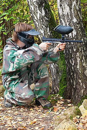 Paintball player is hiding and shooting aside