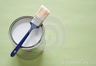 Paintbrush and can of paint on green background