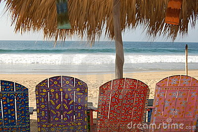 Painted chairs on beach.