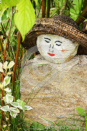 Painted face on rock garden decoration