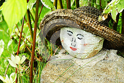 Painted woman face on rock