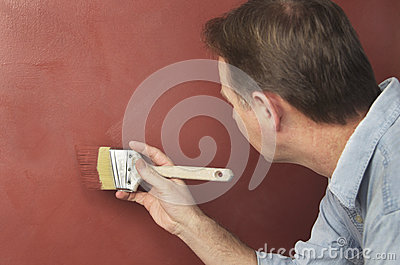 Painter Brushing Textured Red Wall