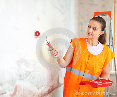 Painter paints wall with roller