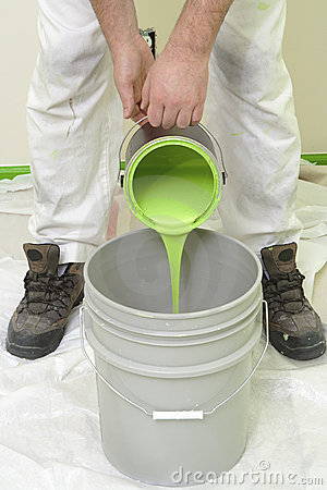 Painter pouring green paint