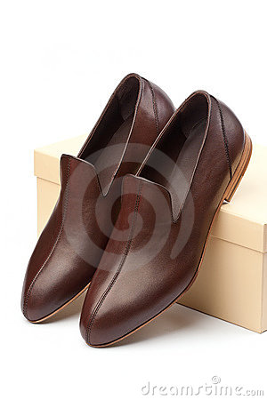 Pair of brown male shoes in front of show box
