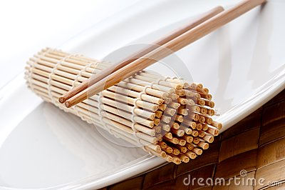 A pair of chopsticks and a sushi mat