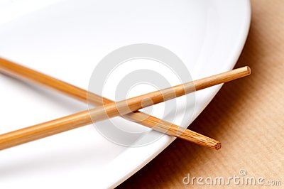 A pair of chopsticks on a white pla