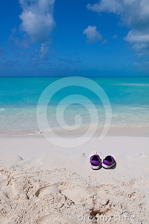 Pair of colored sandals on a white sand beach