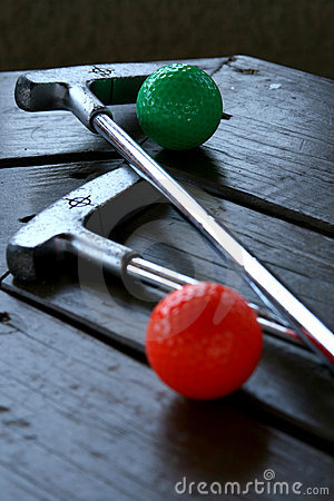 Pair of crazy golf clubs with golf balls