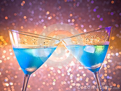 A pair of glasses of  fresh blue cocktail with ice make cheers