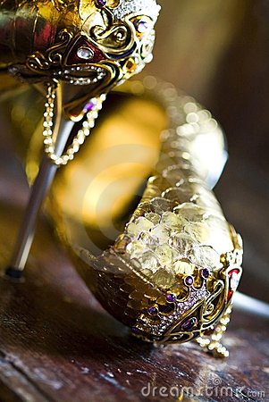 Pair of jeweled golden shoes in antique interior