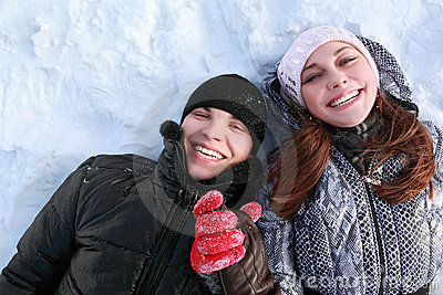 Pair of lovers people lies on snow and laugh