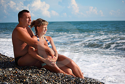 Pair sit on pebble beach