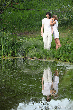 Pair stands on bank of pond