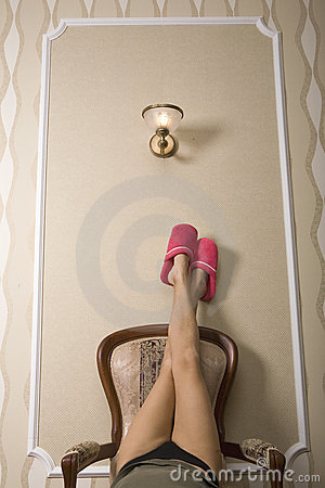 Pair of a Woman s Feet over Chair  with Red Sh