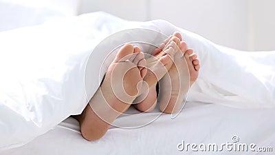 Paires de pieds jouant le footsie sous les couvertures banque de vidéos