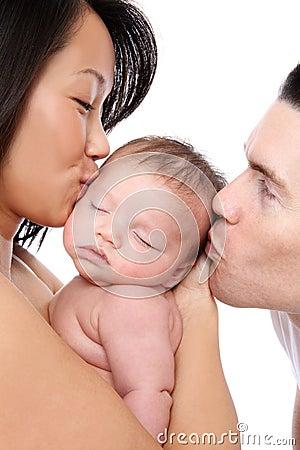 Pais que beijam o bebê
