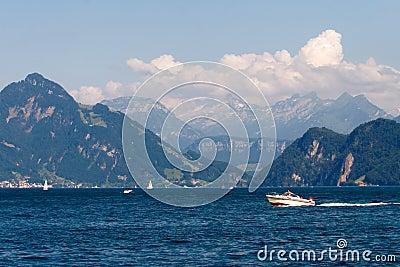 Paisagem com lago, veleiros e montanhas