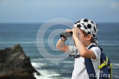 Paisagem de exploração do mar do rapaz pequeno com binóculos