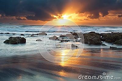 Paisaje de la salida del sol del océano con las nubes y las rocas de ondas