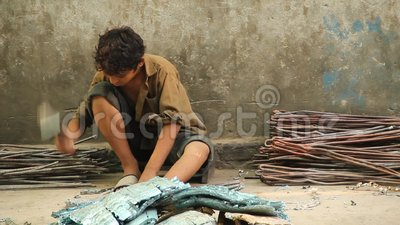 Child Labor in Pakistan. Pakistan - Gujranwala 2014: A child separating copper pipes from car radiators with the help of sharp hammer in Gujranwala, Pakistan stock footage