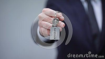 Palabra de la seguridad en llavero en la mano del hombre de negocios, sistema de seguridad casero, servicio del guardia metrajes