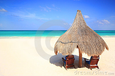 Palapa thatch umbrella and chairs on beach