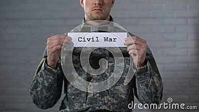 Palavra da guerra civil escrita nas mãos do sinal dentro do soldado masculino, da crueldade e da morte vídeos de arquivo