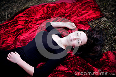 Pale woman in black dress lying on red carpet