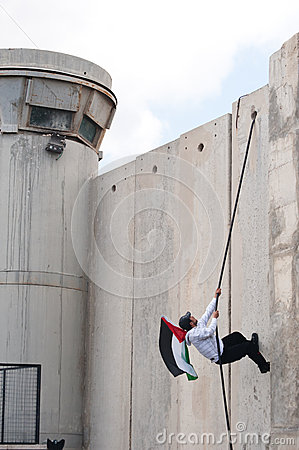 Palestinian climbs Israeli separation wall Editorial Photography