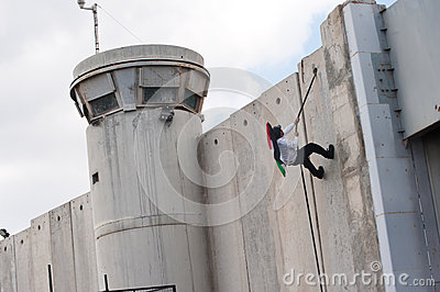 Palestinian climbs Israeli separation wall Editorial Stock Image